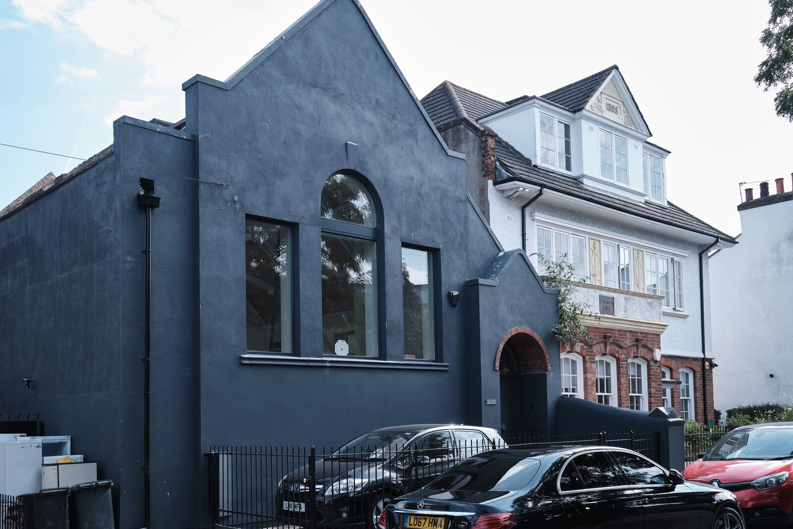 Outside, the facade is painted in a moody tone that contrasts with the lightly colored interior. A gated area provides dedicated, off-street parking.  Photo 14 of 14 in This Former Chapel, Now a Heavenly Artist's Studio and Home, Lists for £1.6M