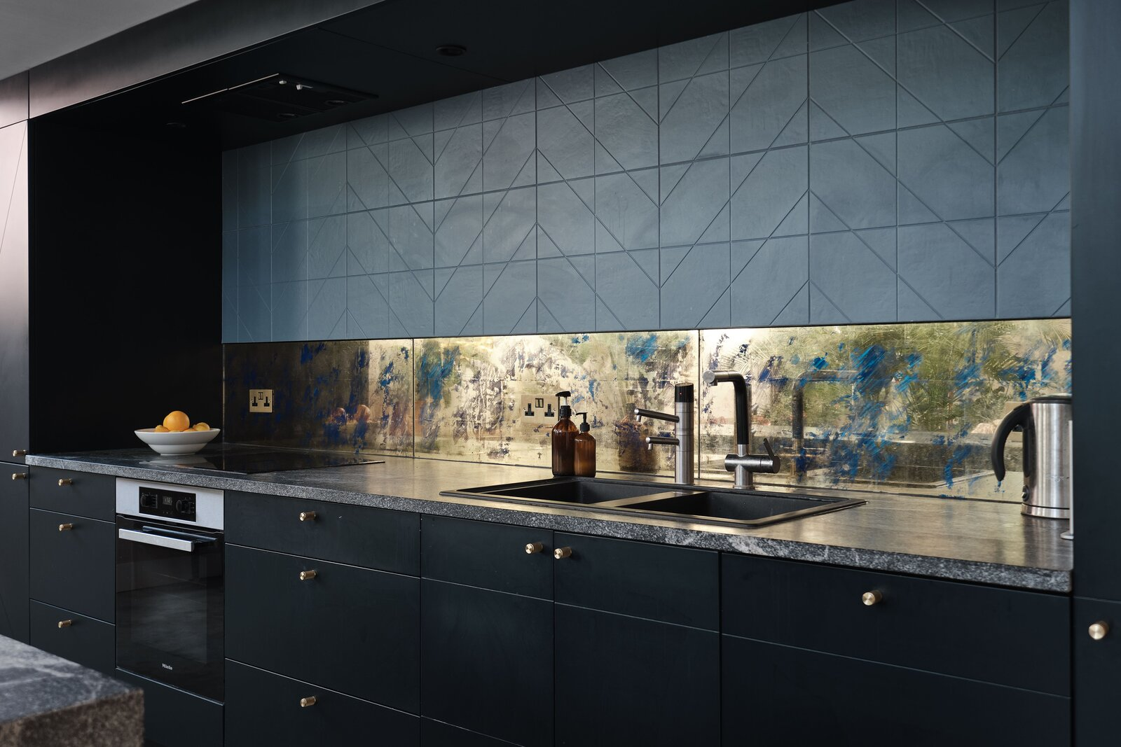 Matte black cabinetry is complemented by the granite clad island and countertops. A gold verre églomisé backsplash was handmade by Martynova.  Photo 6 of 14 in This Former Chapel, Now a Heavenly Artist's Studio and Home, Lists for £1.6M