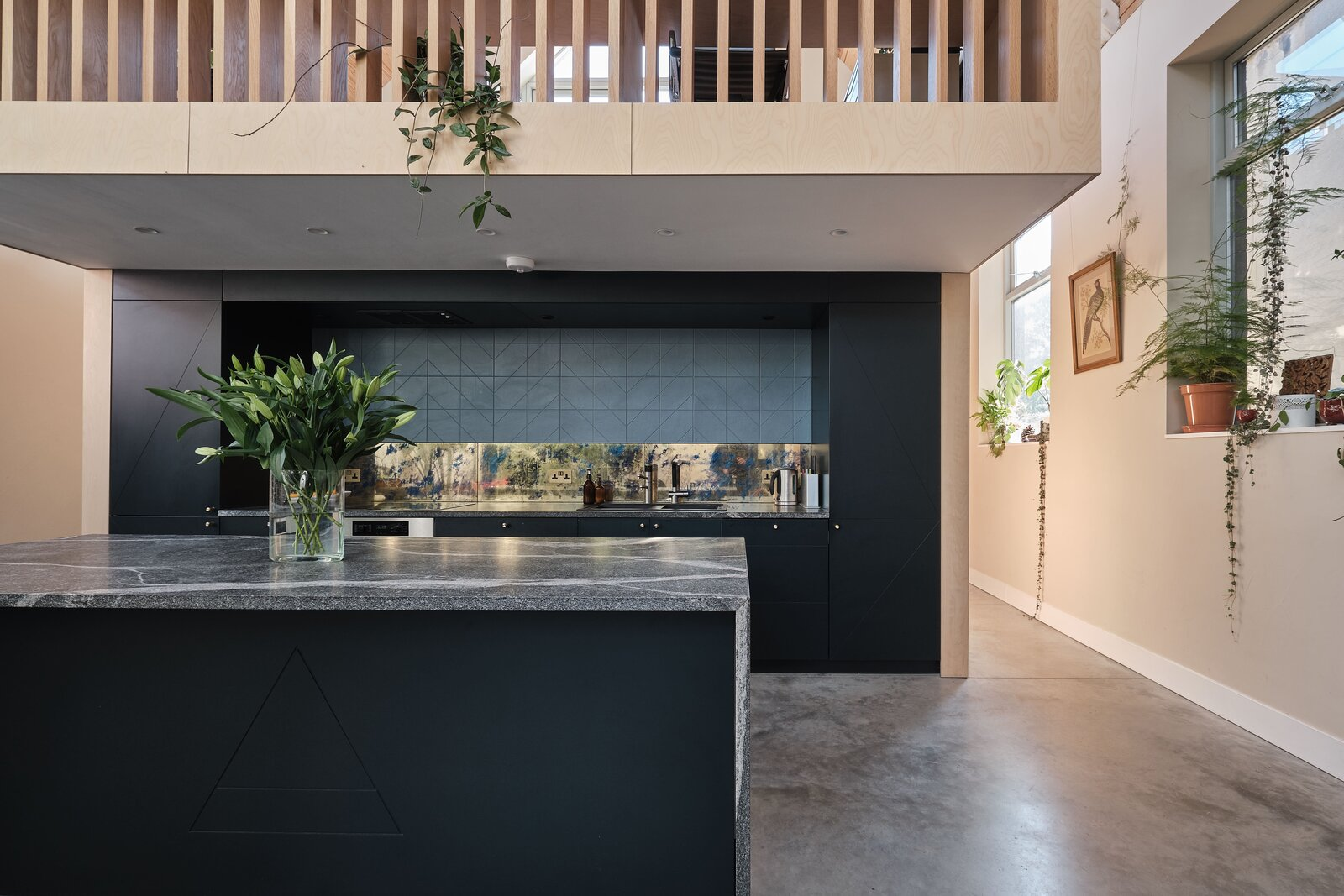"""The mezzanine cantilevers over the kitchen. """"The material palette of oak, birch plywood, oiled pine and stone add a textural richness to the space which balance the interventions against the simplicity of the original building,  Photo 5 of 14 in This Former Chapel, Now a Heavenly Artist's Studio and Home, Lists for £1.6M"""