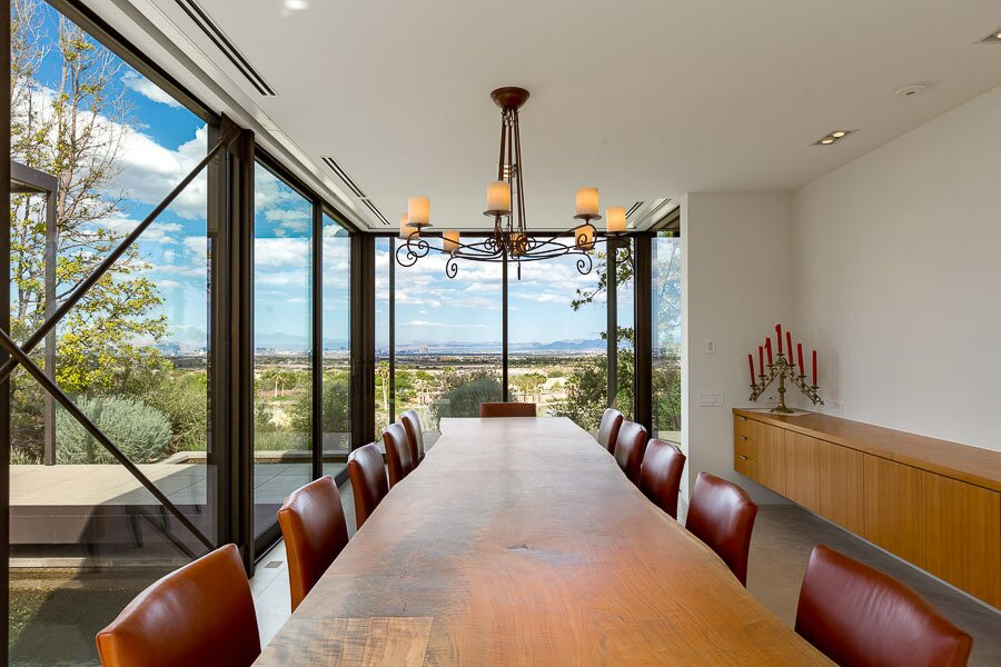 """The home's two wings divide public and private spaces on either side of the living area. Here, a formal dining area looks toward distant views of the Las Vegas Strip.  Photo 5 of 12 in Asking $10.5M, This Desert Prefab by Marmol Radziner Doesn't Want for """"Wow"""" Factor"""