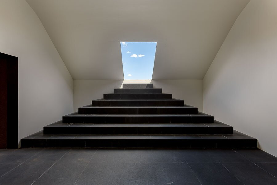 """Inside the Turrell-designed concrete structure, stairs descend into a sequence of subterranean observation rooms, each of which are illuminated by colored lights during sunrise and sunset. Shown here, the first room looks back to framed views through the entryway, while an adjacent space (not pictured) provides skyward views through an opening in the ceiling.   Photo 2 of 12 in Asking $10.5M, This Desert Prefab by Marmol Radziner Doesn't Want for """"Wow"""" Factor"""