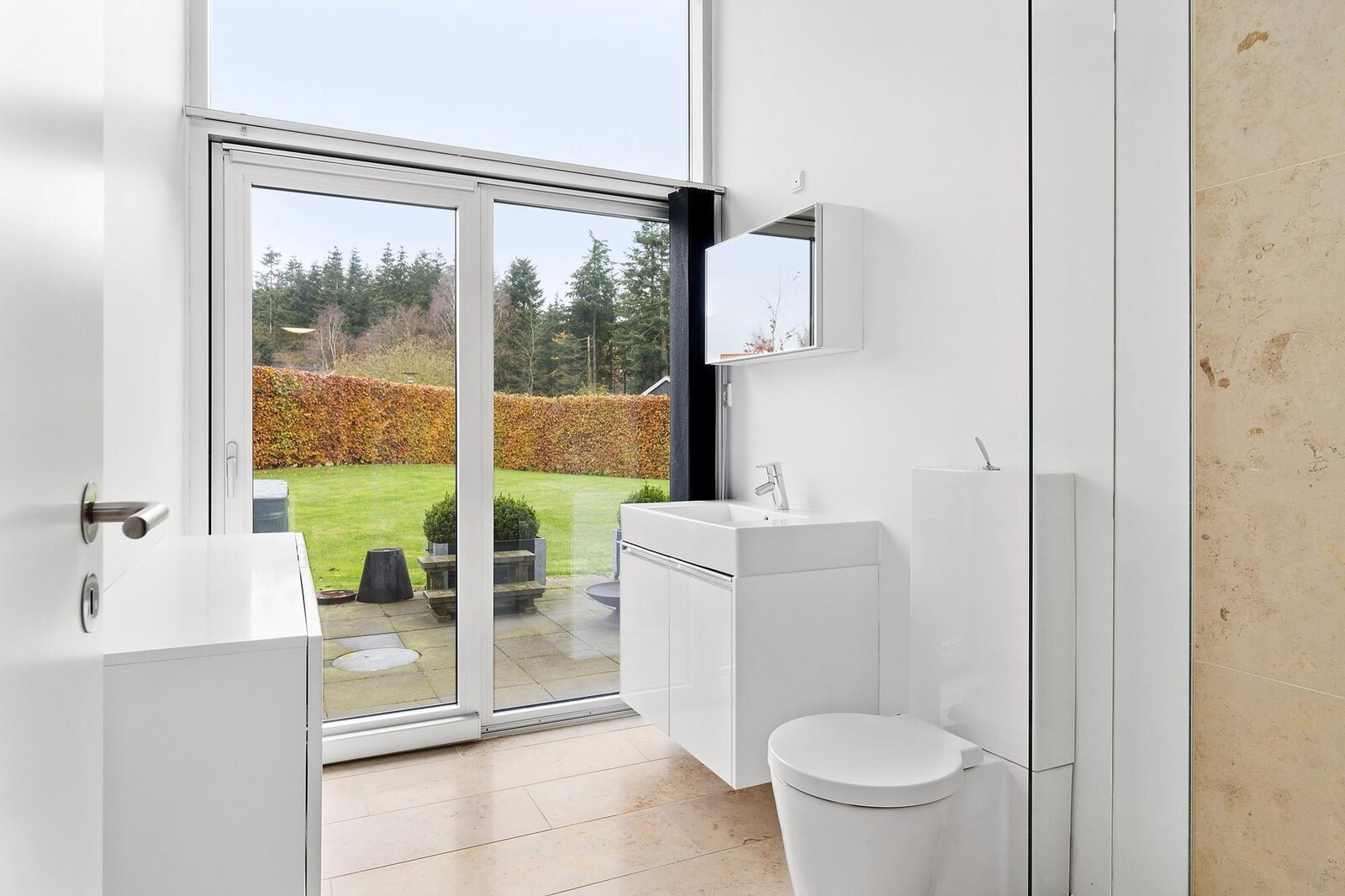 A look at one of the home's full bathrooms, which also provides direct access to the rear patio.  Photo 7 of 10 in Bjarke Ingels's Hobbit-Esque Hill House Lists for $715K