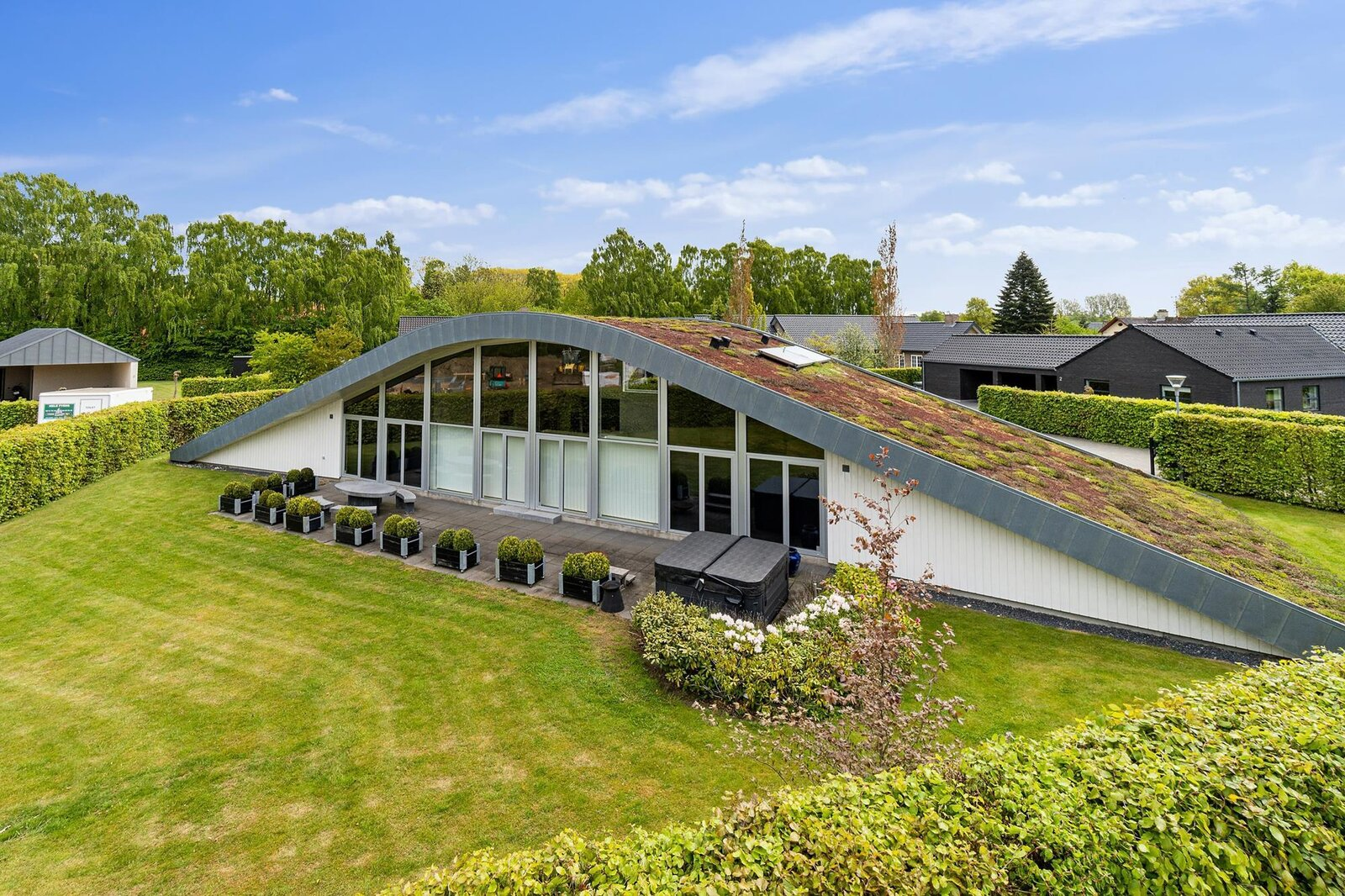 Another view of the front facade shows the green roof that tapers into the yard at each end. Sedum, a low-maintenance grass was installed along the roof by Sweden-based Veg Tech.  Photo 8 of 10 in Bjarke Ingels's Hobbit-Esque Hill House Lists for $715K