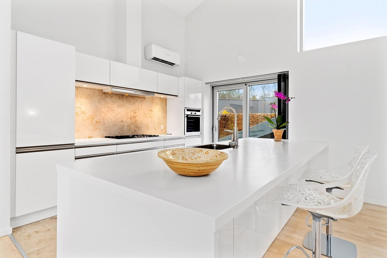 The all-new kitchen features a large island, updated appliances, and Corian countertops.  Photo 4 of 10 in Bjarke Ingels's Hobbit-Esque Hill House Lists for $715K