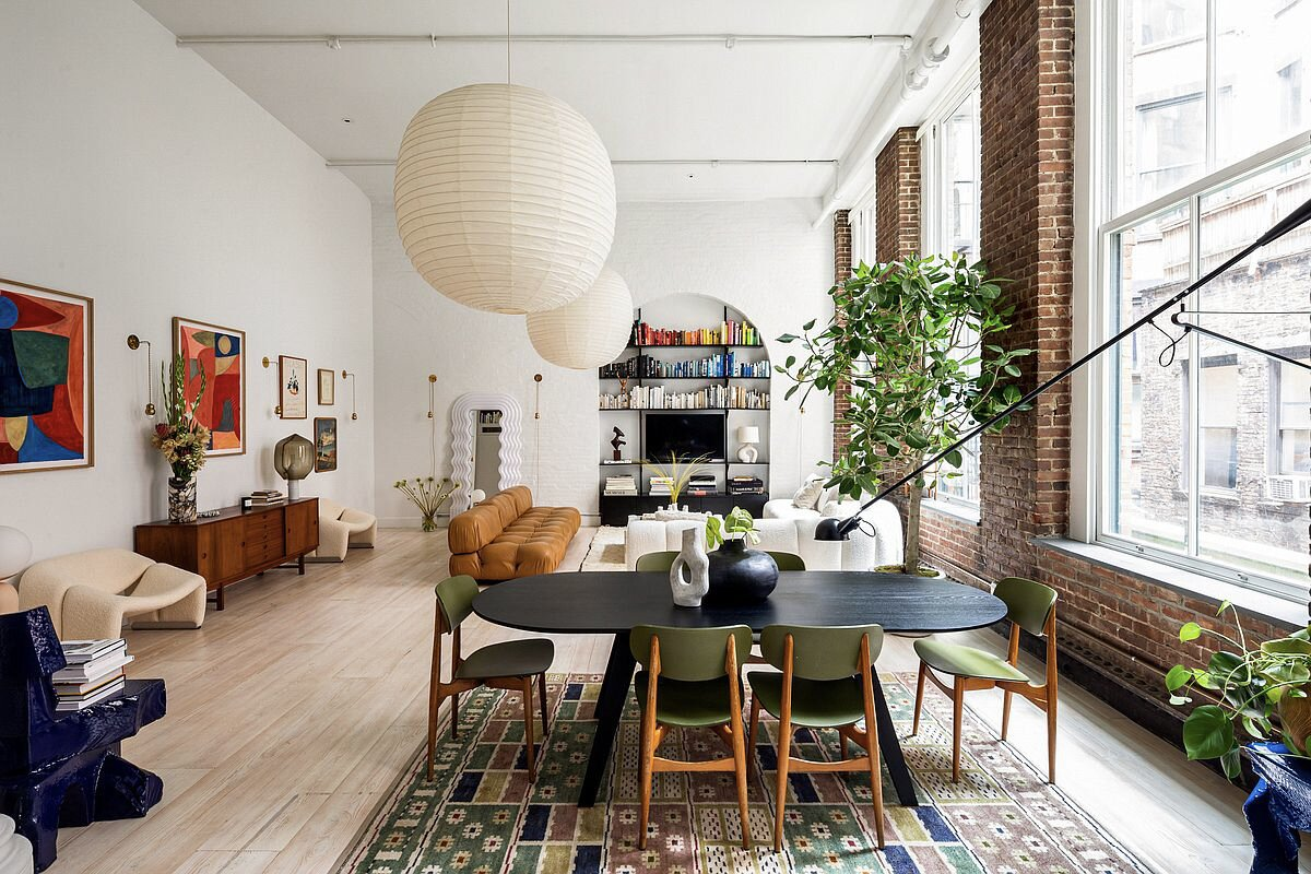 Hosk's designer finds included a bouclé Bernhardt sectional that she spotted on Instagram, as well as a Mario Bellini modular sofa and a vintage credenza. A dining table by Ilse Crawford and a rug from Swedish designer Märta Måås-Fjetterström sit underneath oversized Isamu Noguchi lanterns. Danish-made, wide-planked hardwood floors run throughout the home.  Photo 3 of 10 in Supermodel Elsa Hosk Lists Her Chic SoHo Loft for $3.5M