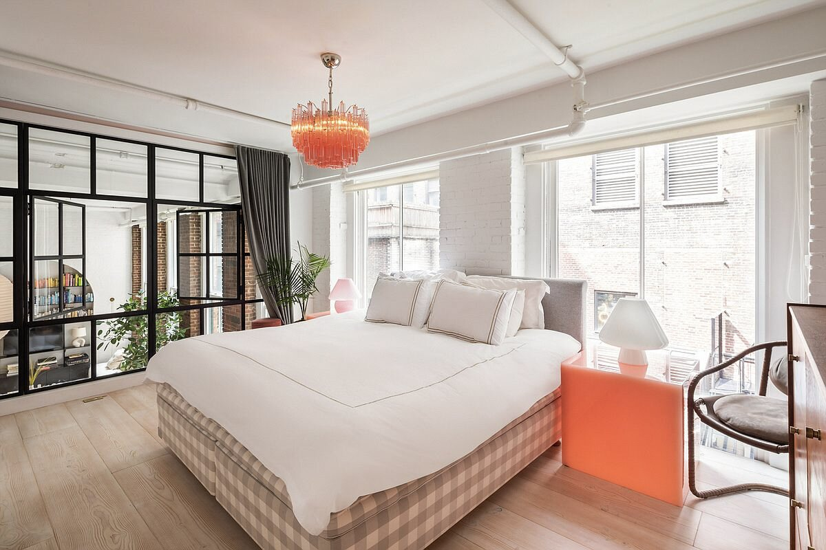 A steel-framed glass wall overlooks the living area from the principal bedroom upstairs.   Photo 6 of 10 in Supermodel Elsa Hosk Lists Her Chic SoHo Loft for $3.5M