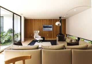 In the living room, an Era sofa from Lytle Pressley joins a Calder coffee table by Minotti and a Grand Repos armchair and ottoman by Antonio Citterio for Vitra. The fireplace is by Fireorb.