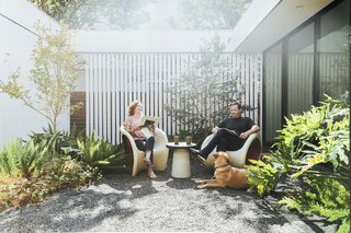 "Accompanied by their dog, Gibson, in the gravel courtyard, Kristin and Jim relax on a Driade MT1 armchair and MT3 rocking chair, both by Ron Arad. ""We value that modern ideal—where you can easily go outside and where small rooms feel bigger,"" says Alter."