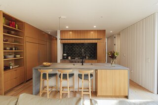 "The kitchen features white oak cabinetry and an island topped with Caesarstone in Rugged Concrete. The Torii stools are from Bensen and the Compendium pendant is from Luceplan,  while the oven is by Wolf and the faucet is by California Faucets. The long white wall was meant for hanging art but so far remains bare. ""It feels like a gallery that was ransacked,"" jokes Jim, ""but we've grown attached to the clean expanse."""