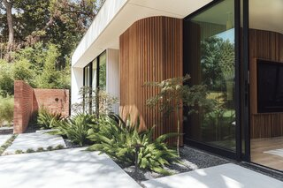 The wood cladding extends outside and wraps around a corner of the facade. Alemán Design Build oversaw the landscaping.
