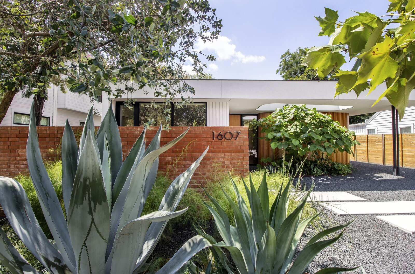 Outdoor, Trees, Walkways, Shrubs, Hardscapes, and Front Yard The Pemberton Residence in Austin, Texas, was designed by local firm Alterstudio with inspiration from California modernist design.  Photo 1 of 12 in This Eichler-Inspired Dwelling in Austin Boasts Serious Curve Appeal