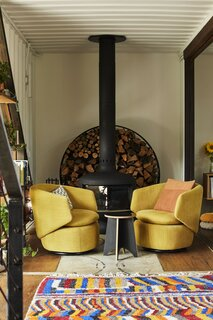 Two mustard Crescent swivel chairs and throw pillows from West Elm add a touch of color to the living area. Under the chairs, a steel plate from the original shipping container reminds everyone what the house used to be. The fireplace is Fire Drum 2 by Malm and the firewood holder is by David DeSantis.