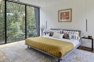 In the couple's bedroom, a Nook upholstered platform bed from Blu Dot is flanked by C Shape end tables from Yamazaki Home.
