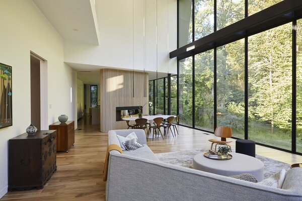 Designed by architects Eric Höweler and Meejin Yoon, the home centers on a soaring living/dining area with warm walnut flooring and large glass walls from Western Window Systems. A vintage Korean chest complements the neutral palette.