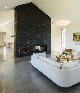 Instead of designing a completely open plan, Berg separated the public rooms with a freestanding fireplace wall made of Mutual Materials bricks in Coal Creek. An Emmy sectional by Egg Collective for Design Within Reach faces a Lars chair from Room & Board