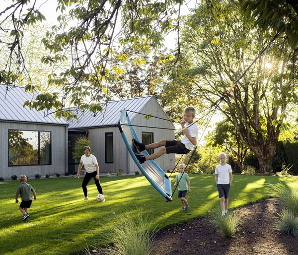 Hilary Severson and her sons play outside their home, designed by architect Solomon Berg. Set amid mature maples on three acres south of Portland, Oregon, the house has a gabled, standing-seam metal roof and rough-sawn and smooth cedar siding.