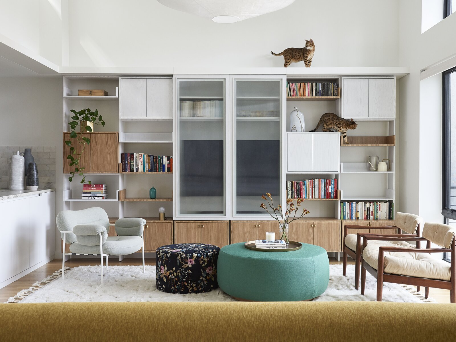 Contemporary furnishings from Muuto and Matter, as well as vintage pieces by Adrian Pearsall, add splashes of color to the couple's cat-friendly living room. The Bollo chair is by Andreas Engesvik and Fogia and the Flowerfield pouf is by Baum und Pferdgarten from Common Seating. The custom ottoman and media cabinet are by Studio Natio, while the Flotation chandelier is by Ingo Maurer.