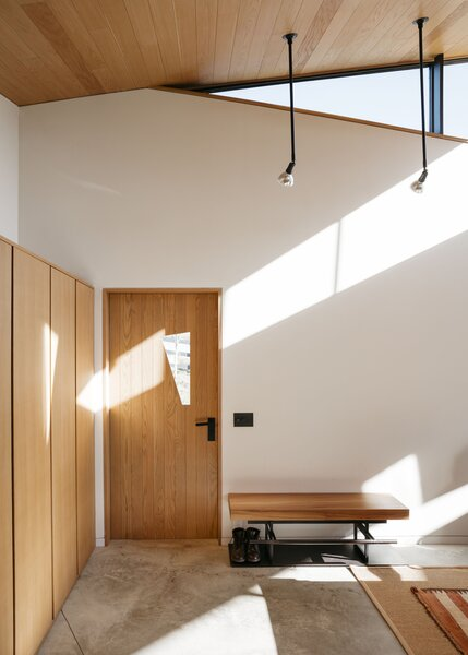 A trapezoidal window in the front door reflects the home's overall geometry. Next to the door, a custom bench by Simon Hamui, who did all the millwork, provides an easy place to lace up boots before heading out for a hike.