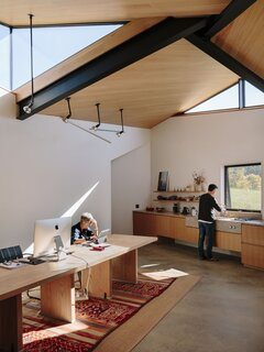 Custom pendants by GRT hang from above in the open kitchen and work area.