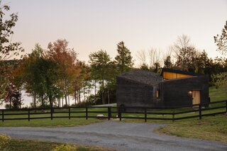 The roof is clad in natural cedar with a copper trim.