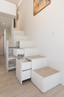 Hidden storage underneath the stairs provides space for an organized kitchen pantry.