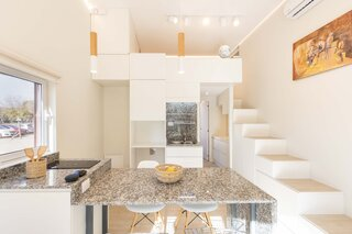 A closer look at the kitchen shows the central countertop that doubles as a dining area.