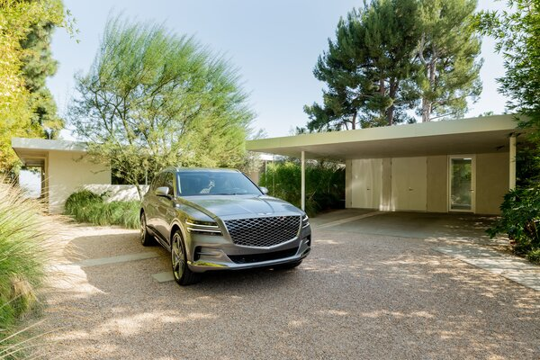The Genesis GV80 sits near the open carport of the Clear Oaks Residence.  Preproduction model with optional features shown.