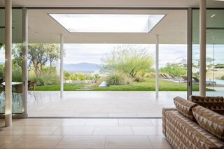 Upon entering the home, the eye is immediately drawn to the full panel of windows and the views beyond.