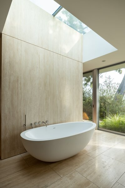 The skylight and floor-to-ceiling glass windows invite nature into the bathing area of the bathroom.