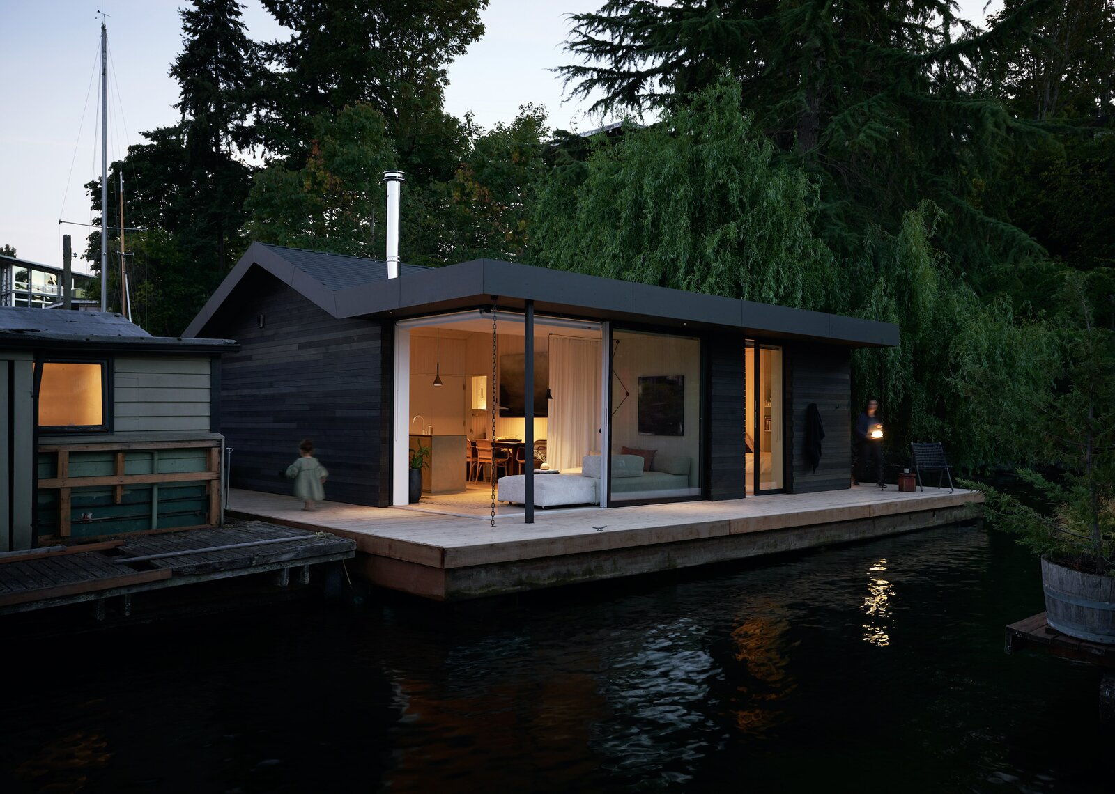 """Exterior, Boathouse Building Type, Cabin Building Type, Small Home Building Type, and Wood Siding Material LaCantina's Zero Post Corner Sliding Glass Doors seamlessly open a corner of the home. """"The large openings make it easier for us to live in a smaller footprint and use the deck as a functional living space,"""" Suzanne adds. """"In that way, the outdoors feel very much part of the interior. It's wonderful.""""  Photo by Kevin Scott  Photo 11 of 13 in This Breezy Floating Home Makes the Most of a Tranquil Setting Along Seattle's Portage Bay"""