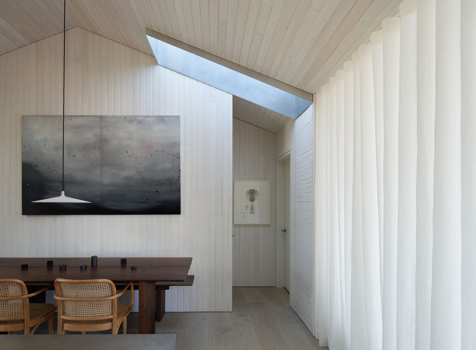 """Dining Room, Light Hardwood Floor, Chair, Pendant Lighting, and Table A sheer curtain divides the living spaces as needed, while another lightwell directs sunlight into the dining area. """"The pendant lights above the island and dining table are actually made of concrete, which I thought was a fun juxtaposition against the lightness of the room and general materials chosen,"""" Suzanne adds.  Photo by Kevin Scott  Photo 7 of 13 in This Breezy Floating Home Makes the Most of a Tranquil Setting Along Seattle's Portage Bay"""