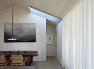 """A sheer curtain divides the living spaces as needed, while another lightwell directs sunlight into the dining area. """"The pendant lights above the island and dining table are actually made of concrete, which I thought was a fun juxtaposition against the lightness of the room and general materials chosen,"""" Suzanne adds.  Photo by Kevin Scott"""