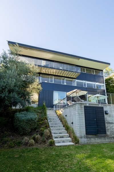 The trilevel home spills onto a grassy knoll that overlooks the Hollywood Hills and Downtown Los Angeles.