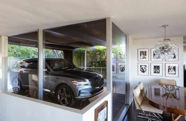 While parked in the carport, automobiles become a part of the interior design. Here, the Genesis GV80 can be seen from the dining area.  Preproduction model with optional features shown.