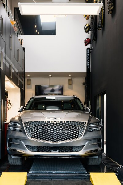 A Genesis GV80 sits on a BendPak High Bay Lift on the ground floor of the garage.  Preproduction model with optional features shown.