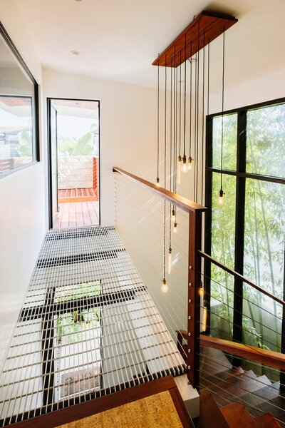 The atrium has an open feel thanks to the metal grating platform, large window along one wall, and staircase with wire banisters.