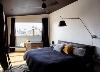 The natural light and blonde flooring brighten the dark color palette of the bedding, chevron rug, and black curtains and ceiling.