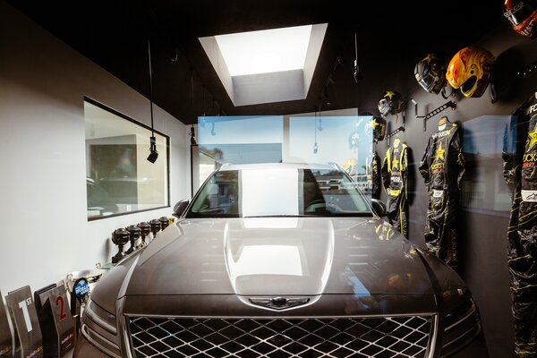 Tanner Foust delights in the surprised expressions on visitors' faces when they first look into the garage trophy room. The Genesis GV80 can be seen through the glass.  Preproduction model with optional features shown.