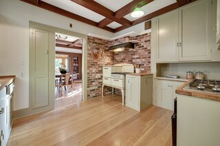 The kitchen features original cabinetry, as well as a vintage stovetop and modern appliances.