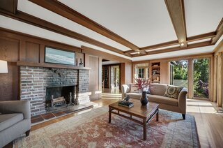 In the adjacent living room, a large hearth features original clinker bricks and a solid redwood mantle. Floor-to-ceiling windows overlook the backyard garden.