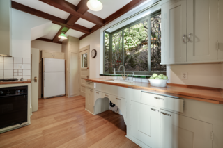 Above the sink is a beveled-glass bay window, and in the corner next to the refrigerator are stairs that lead to the lower level.