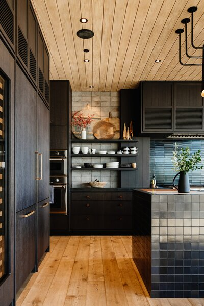The kitchen features oak cabinets stained in a dark grey and navy tile from Heath Ceramics. These darker elements are balanced by the tongue-and-groove wood ceiling and floors, as well as ample sunlight entering through the steel-framed glass doors.