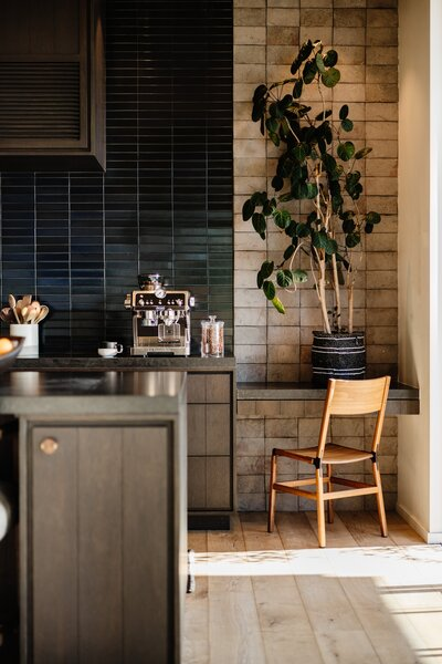Flanking both sides of the backsplash are grey Heath tiles that were installed backwards to reveal the unglazed side. Leathered granite countertops add yet another contrasting texture within the space.