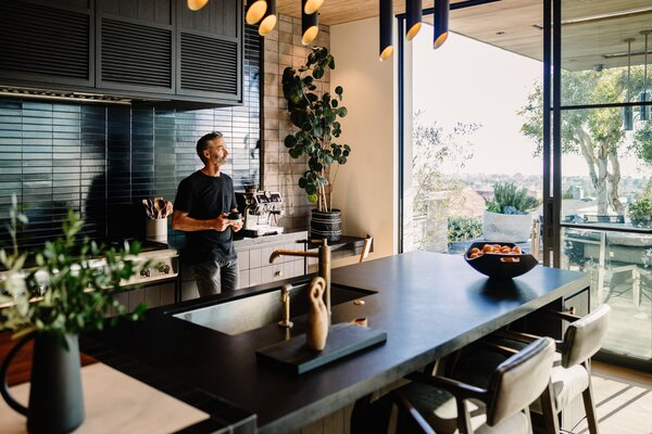 """Olsen enjoys a cup of coffee made by the La Specialista machine. """"It's the perfect fit in a kitchen that is personalized for our own style and life,"""" he comments."""