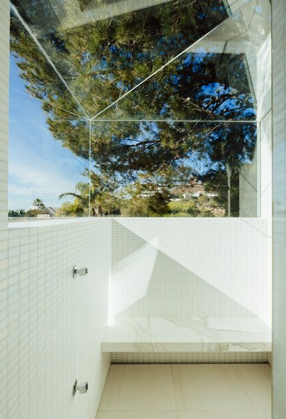 There is a spa-like quality to this shower, with its marble seating, white tile, and faceted glass enclosure.