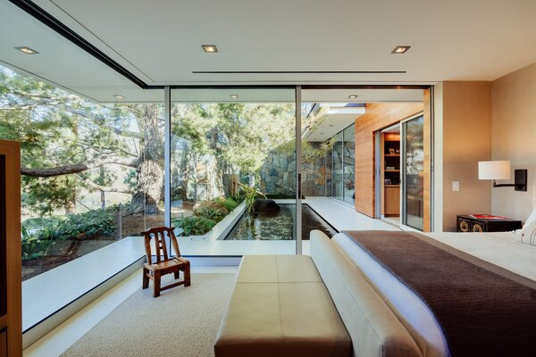 The home's bedrooms connect with calming outdoor areas through large glass panels.