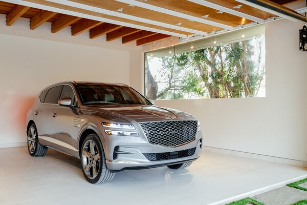 The garage is an integral part of the architecture with its exposed wooden beams and large picture window. Natural light fills the interior, where a Genesis GV80 is parked.   Preproduction model with optional features shown.