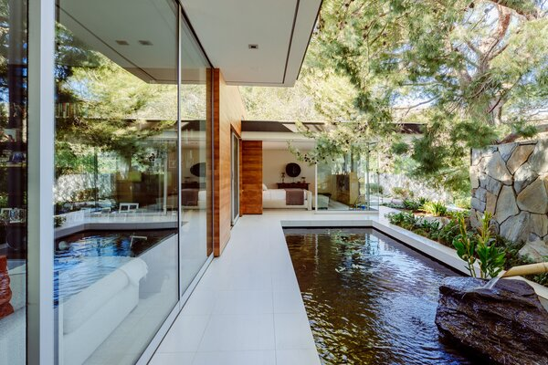 The sophisticated landscape of greenery and water elements add to the escapist nature of the home.
