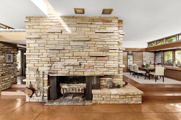 A skylight above the fireplace casts sunlight onto the stacked stone fireplace. A raised dining area is located to the right, while a playroom and the kitchen can be accessed from the left.