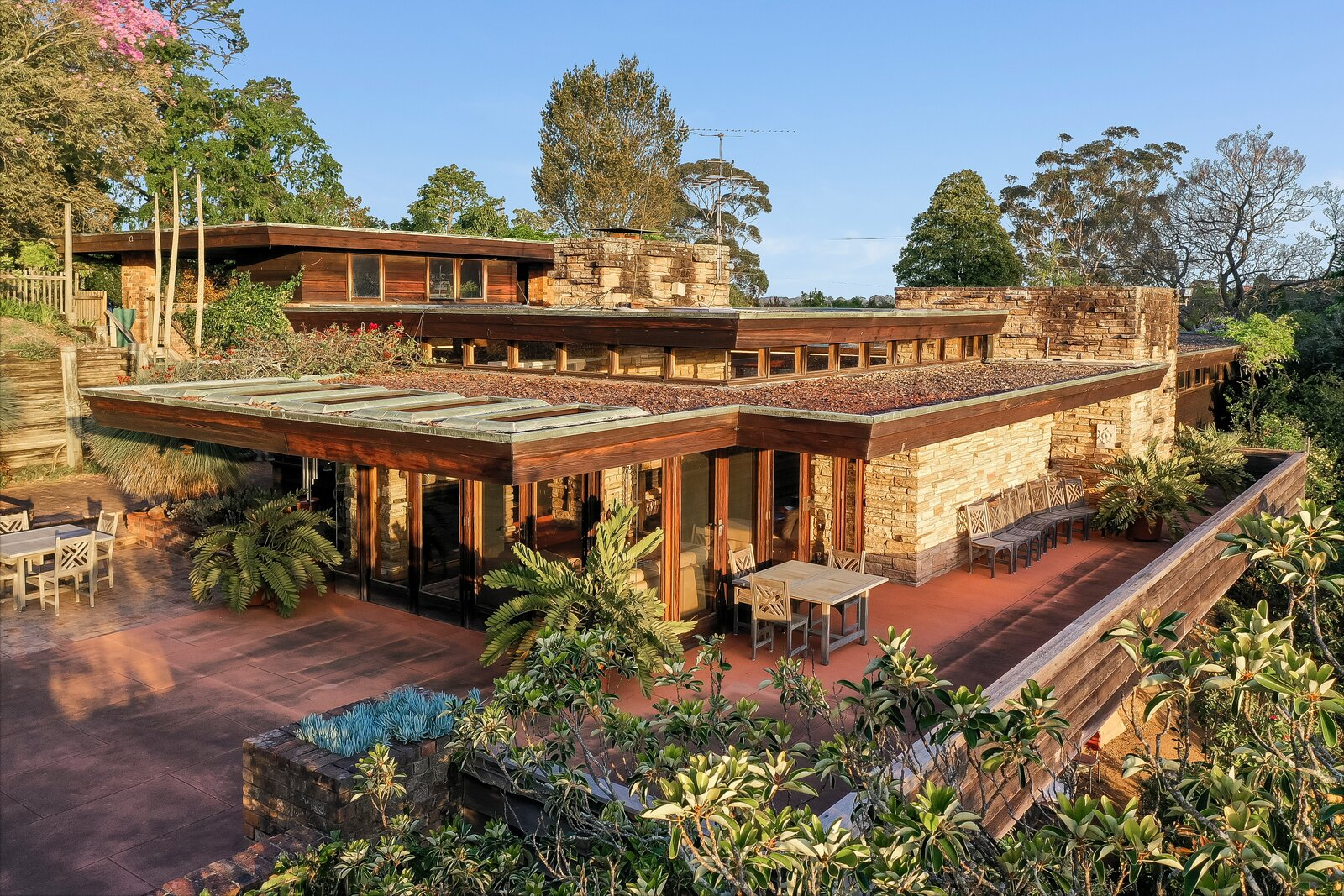A large, cantilevered balcony wraps around the living area and provides ample outdoor space for entertaining, as well as sunset views over the five-acre plot and an adjacent town park.